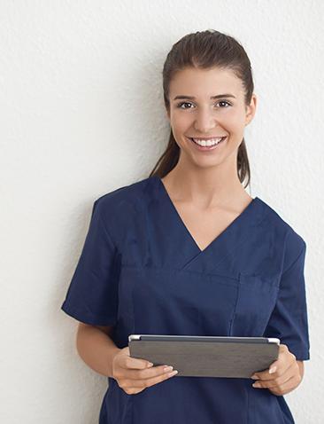 Weibliche Angestellte im Gesundheitswesen / Krankenschwester/Krankenpflegerin, lächelt in die Kamera und hält Dokument